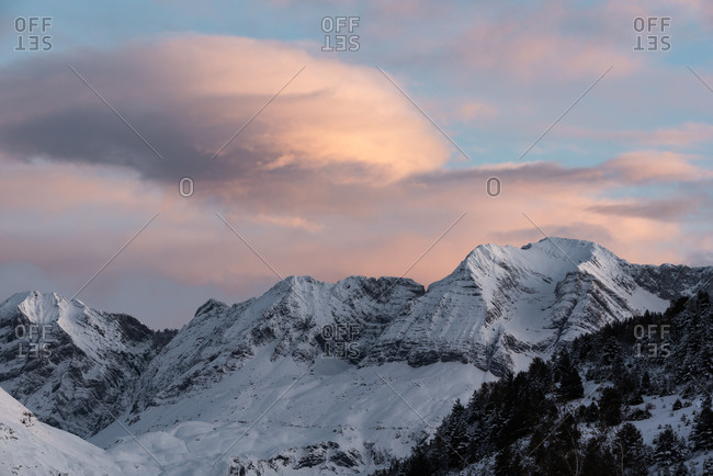 Spectacular scenery of Pyrenees mountain range covered with snow against cloudy sky in winter