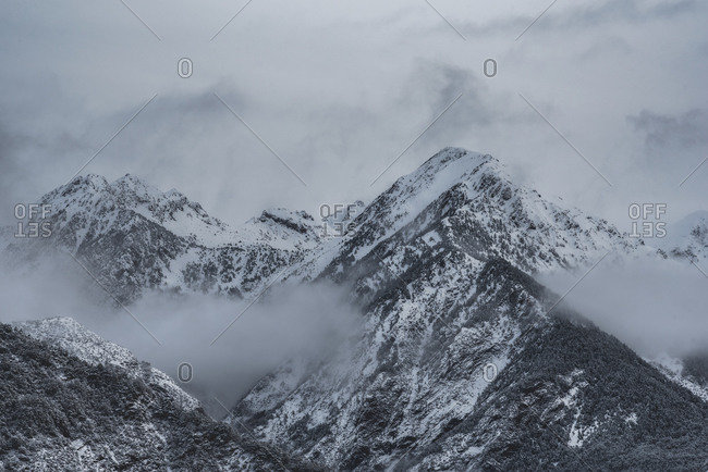 Low angle of spectacular scenery of Pyrenees mountain range covered with snow against cloudy sky in winter