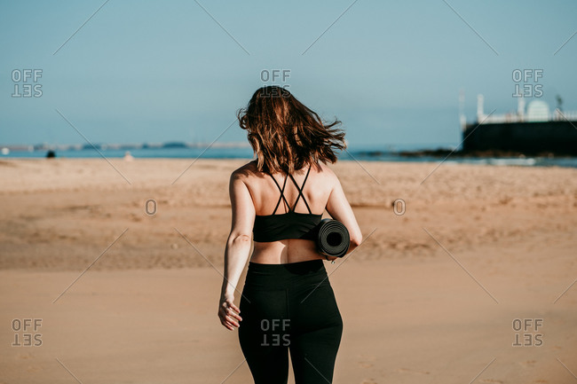 Back view of slim unrecognizable female in sportswear and with yoga mat walking along beach near river on sunny day