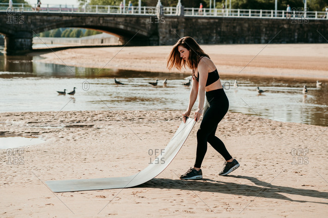 Side view of slender female in bra and leggings putting yoga mat on sandy beach and preparing for doing exercises