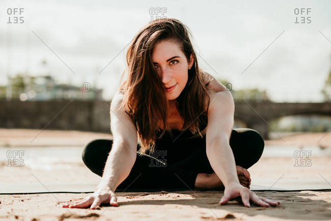 Smiling flexible female sitting on mat in Janu Sirsasana and doing forward bend while looking at camera and practicing yoga on beach in summer