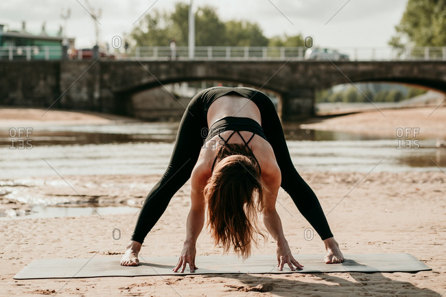 Unrecognizable fit female in sportswear practicing yoga and standing on mat on beach in Prasarita Padottanasana