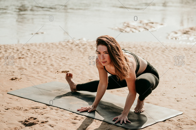 Tranquil female practicing yoga in Side Lunge with Arms Extended pose while standing looking away on mat on beach in summer