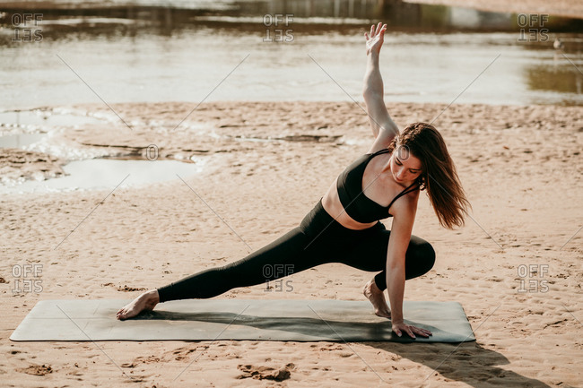 Tranquil female practicing yoga with closed eyes in Side Lunge with Arms Extended pose while standing on mat on beach in summer