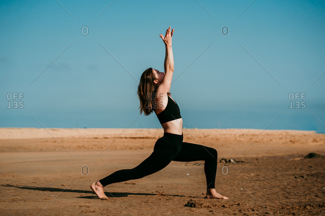 Slim female in sportswear standing on sandy beach in High Lunge Crescent Variation Pose and practicing yoga while looking up