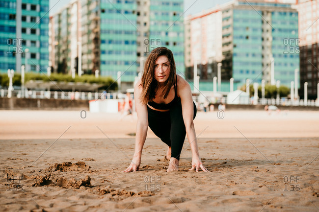 Female standing in High Lunge looking at camera while doing yoga on the beach