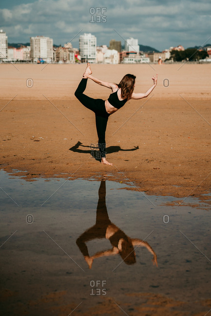Side view of flexible unrecognizable female standing on sandy shore of river in Natarajasana and practicing yoga while balancing on leg