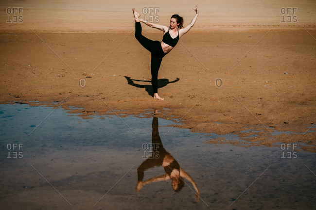 Side view of flexible female standing on sandy shore of river in Natarajasana and practicing yoga while balancing on leg with eyes closed