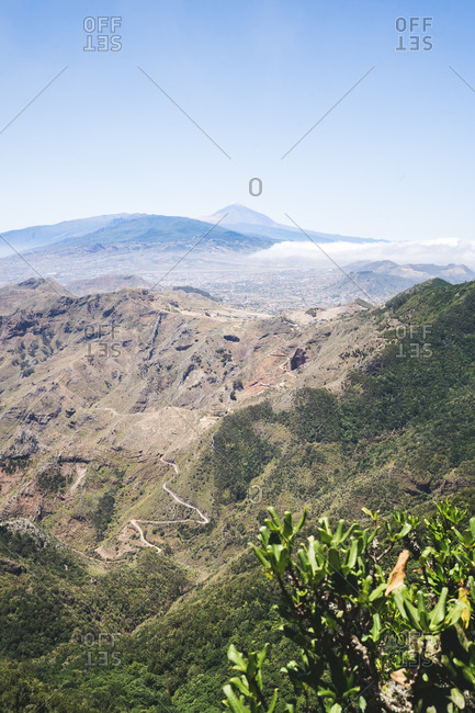 Breathtaking view of highland area with rocky mountains and green hills under blue sky in Tenerife