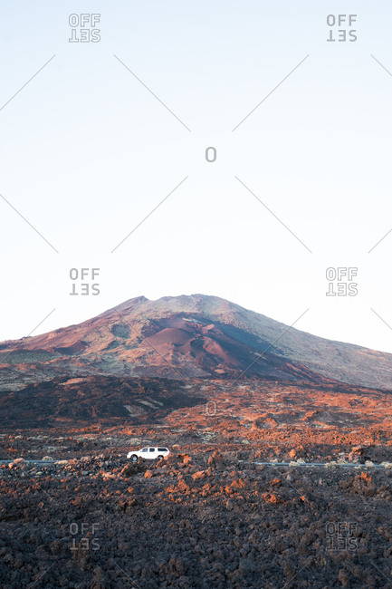 Car driving throughout magnificent landscape of dry rocky valley and mountain range under blue cloudless sky at sundown in Tenerife
