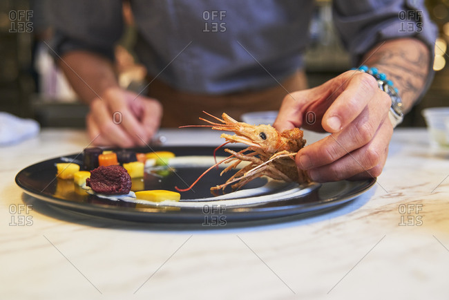 Crop anonymous chef with tongs arranging colorful edible blossoms on plate while garnishing sophisticated dish in restaurant kitchen