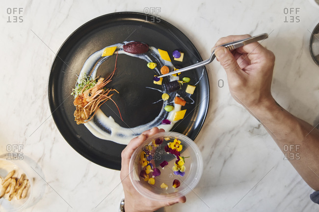 From above of crop anonymous chef with tongs arranging colorful edible blossoms on plate while garnishing sophisticated dish in restaurant kitchen