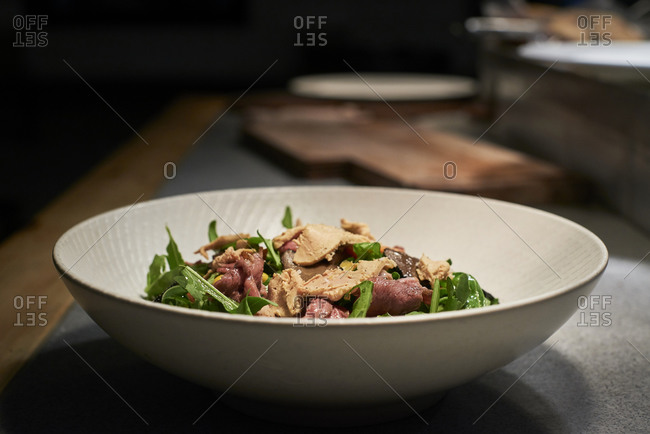 Bowl with delicious salad made with meat and fresh green rocket leaves placed on kitchen counter in restaurant