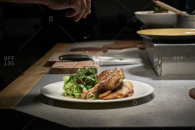 Crop cook adding condiment on tasty chicken leg and potato pieces served with vegetable salad on plate in kitchen of restaurant