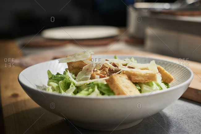 Bowl with delicious salad made with meat, cheese and fresh green salad leaves placed on kitchen counter in restaurant