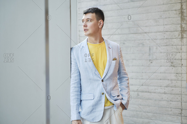 Serious male entrepreneur wearing trendy jacket standing with hand in pocket in bright workplace and looking away