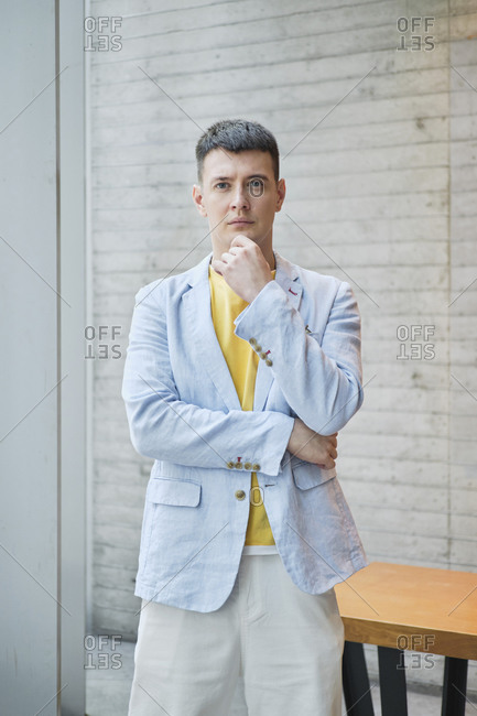 Serious male entrepreneur wearing trendy jacket standing with hand in pocket in bright workplace and looking at camera
