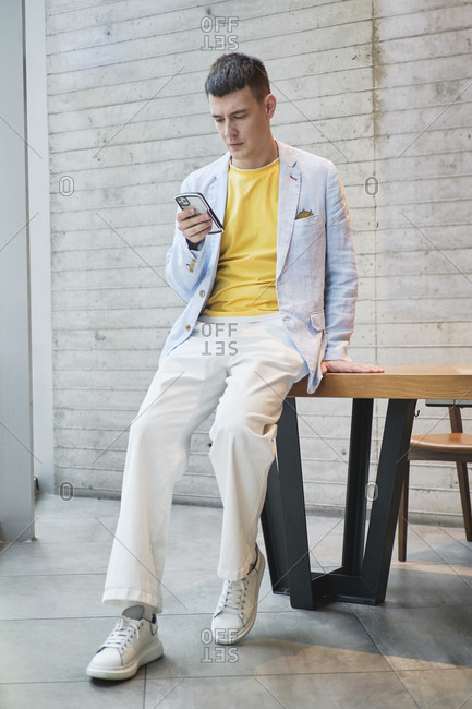 Serious male entrepreneur wearing stylish clothes leaning on table in bright workplace and browsing cellphone
