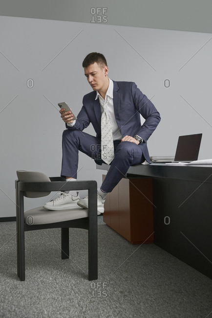 Busy male entrepreneur sitting on table with legs on chair in workplace and using smartphone while looking away