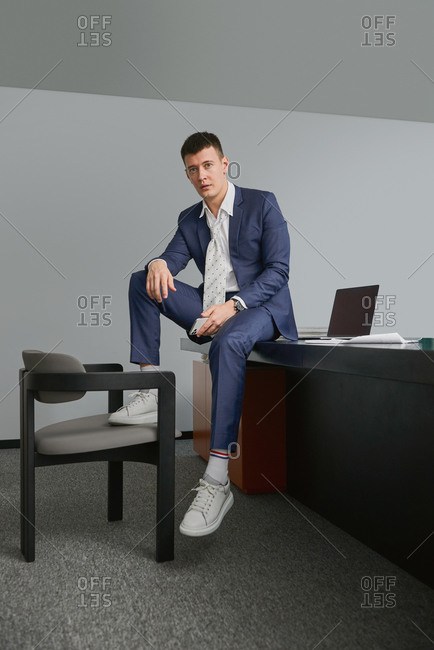 Male entrepreneur sitting on table with legs on chair in workplace looking at camera on office