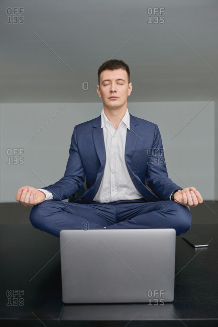 Peaceful male entrepreneur sitting on table in Lotus pose with mudra hands and meditating during hard working day