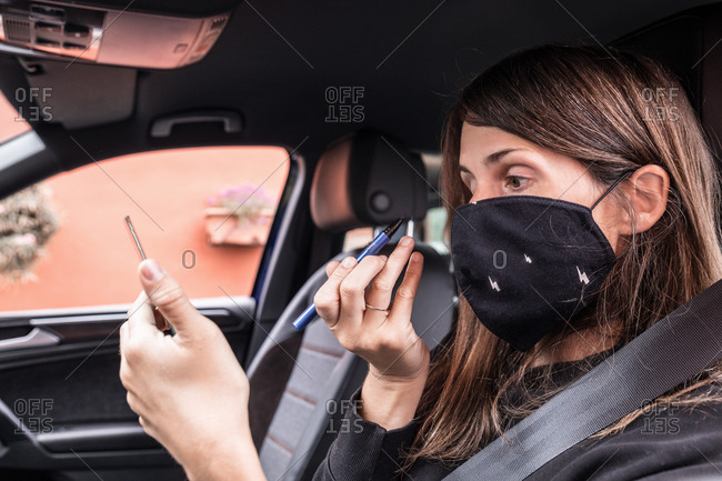Side view of female in protective mask sitting on driver seat and applying eyeliner while looking in pocket mirror
