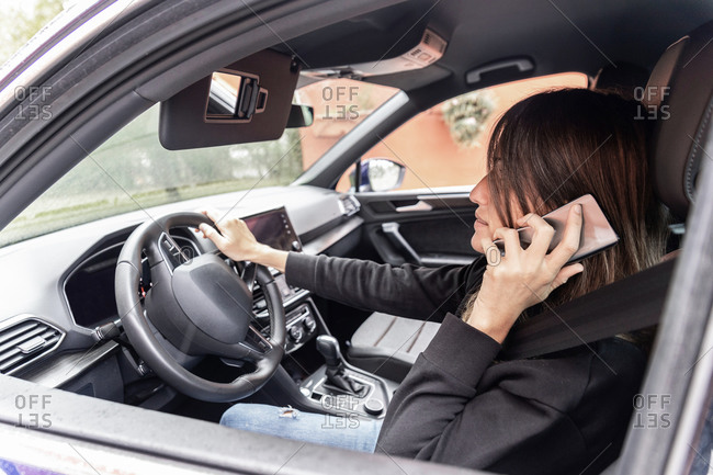 Side view of female entrepreneur in formal jacket sitting on driver seat and discussing project while speaking on smartphone