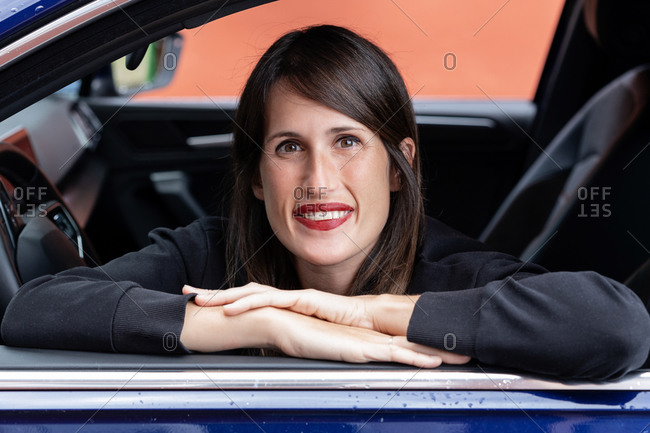 Cheerful female driver leaning on automobile while sitting in car and looking at camera
