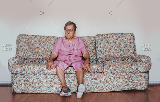 Front view of a senior woman with Alzheimer's mental health issues sitting in a sofa alone in her home