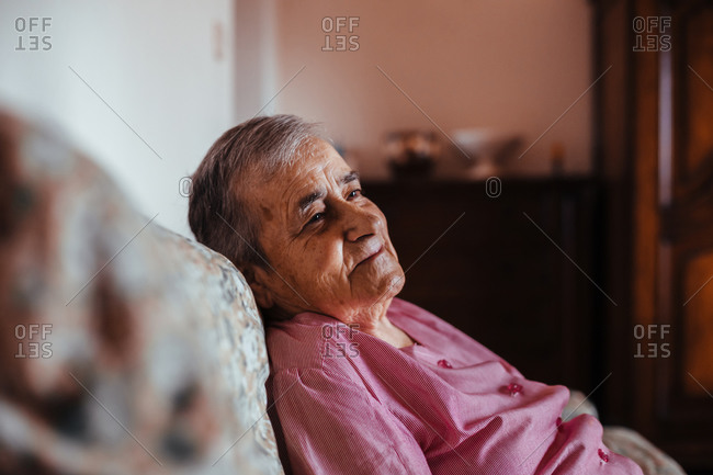 Side view of a senior woman with Alzheimer's mental health issues sitting in a sofa alone in her home