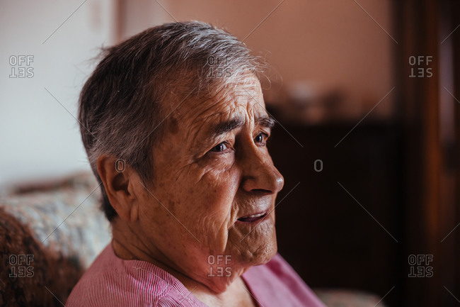 Portrait of a senior woman with Alzheimer's mental health issues sitting in a sofa alone in her home
