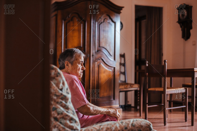 From behind senior woman with Alzheimer's mental health issues sitting in a sofa alone in her home