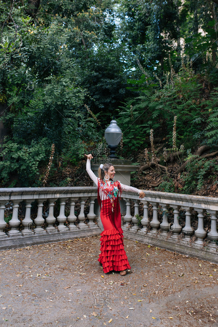 Full body graceful young female in typical elegant red gown performing Flamenco dance with arm raised on terrace with aged fence against green trees