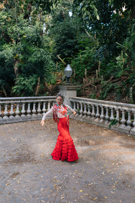 Full body graceful young female in typical elegant red gown performing Flamenco dance on terrace with aged fence against green trees