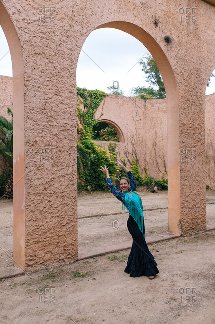 Full body elegant female artist in blue outfit performing traditional Spanish Flamenco dance near arched passage in yard of historic building