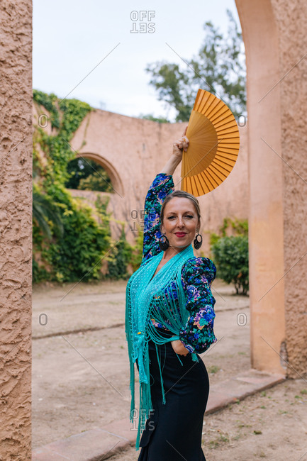 Gorgeous female Flamenco dancer in colorful garment with open fan while standing against blurred old stone wall with arched passage
