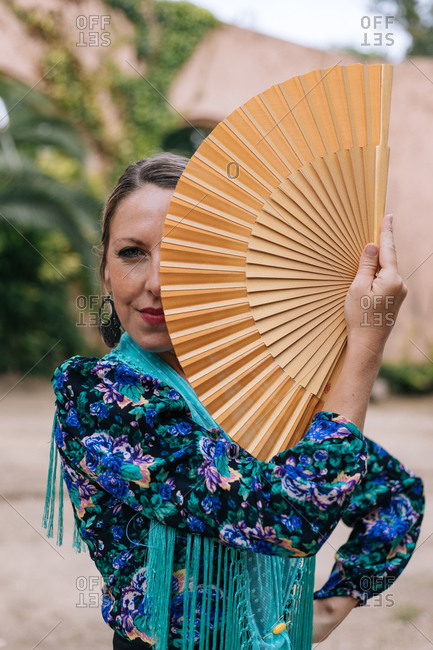Gorgeous female Flamenco dancer in colorful garment covering half of face with open fan while standing against blurred old stone wall with arched passage