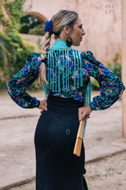 Back view slim woman wearing typical ruffled skirt with colorful blouse and accessories dancing Flamenco on street