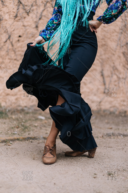 Crop anonymous slim woman wearing typical ruffled skirt with colorful blouse and accessories dancing Flamenco on street