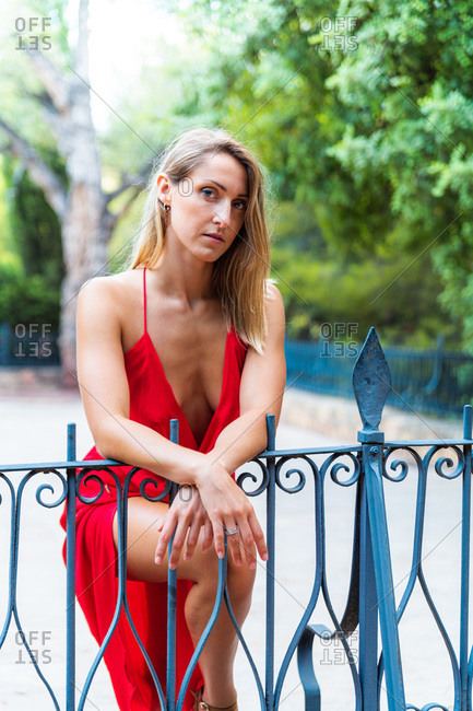 Emotionless female wearing red dress standing near metal railing in park and seductively looking at camera