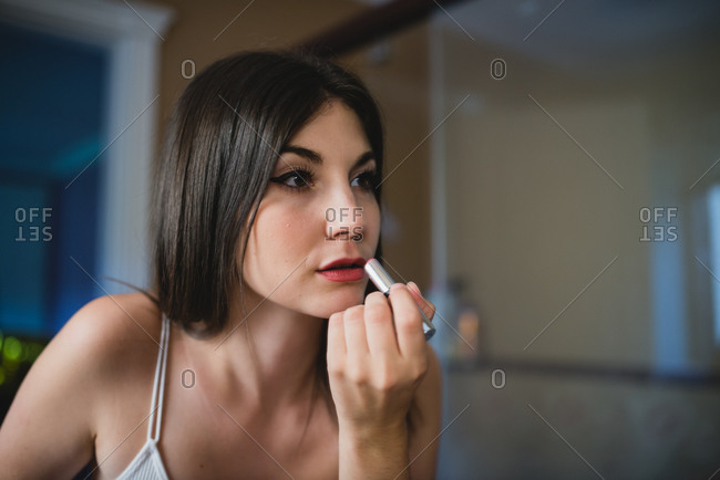 Concentrated charming female with smooth skin applying red lipstick while preparing for event