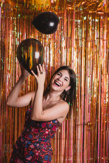 Cheerful female in sparkling dress with balloons while standing near foil tinsel and looking at camera during New Year party