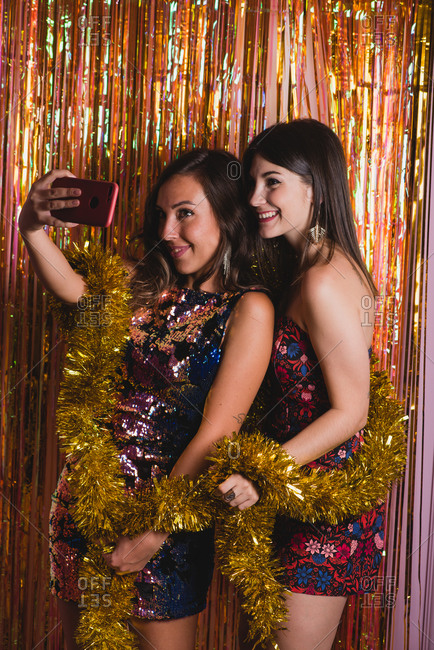 Delighted female friends in festive dresses and with golden tinsel taking selfie on smartphone camera while having fun during New Year celebration
