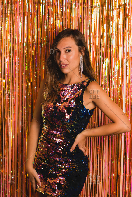 Cheerful female in sparkling dress standing near foil tinsel and looking at camera during New Year party