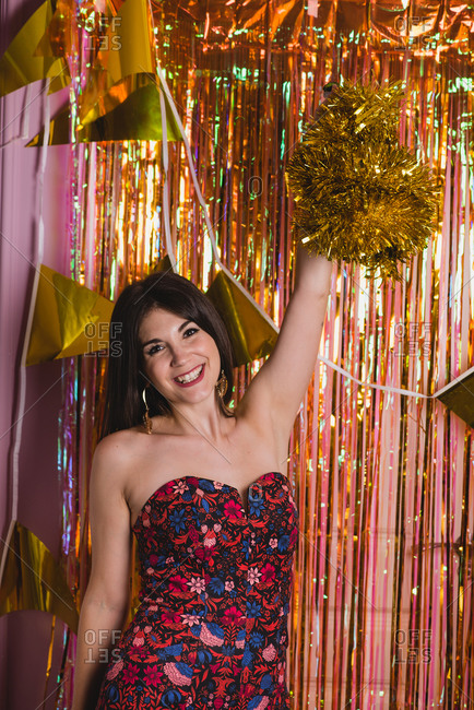 Cheerful young female in festive dress standing near foil tinsel having fun during New Year celebration