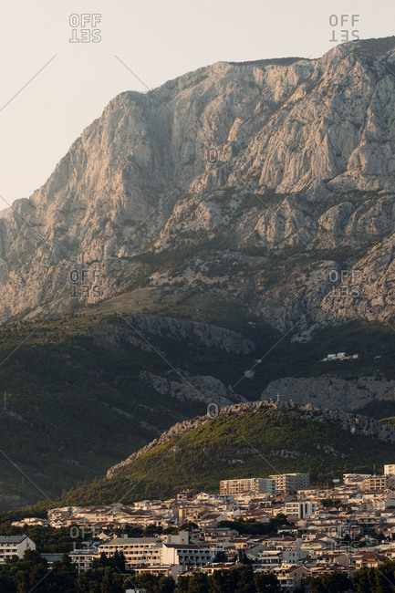 Picturesque landscape of small town surrounded by rough mountains lit by morning light in Croatia