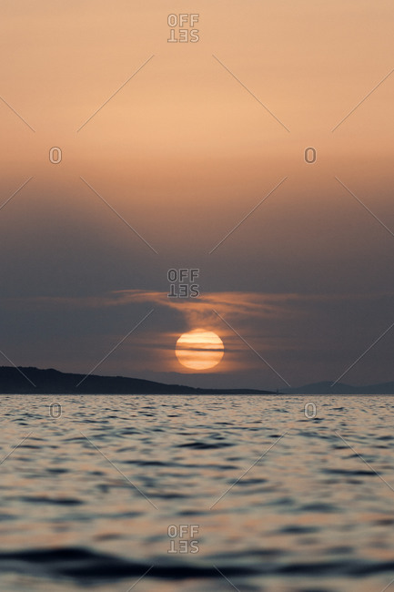 Scenery of calm sea with rippling water reflecting sunlight at sundown in Croatia