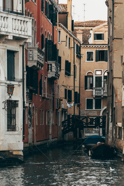 Cityscape of Venice with water canal and old buildings with weathered facade in morning
