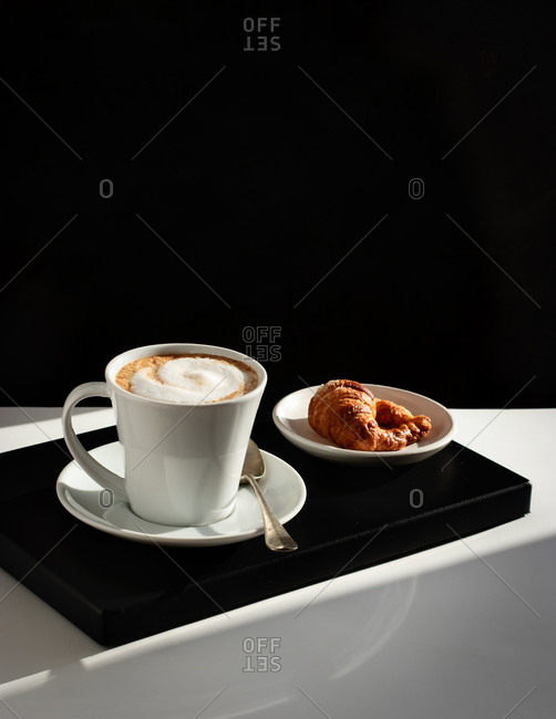 Served white ceramic cup with fresh coffee topped with milk froth and croissant on dish