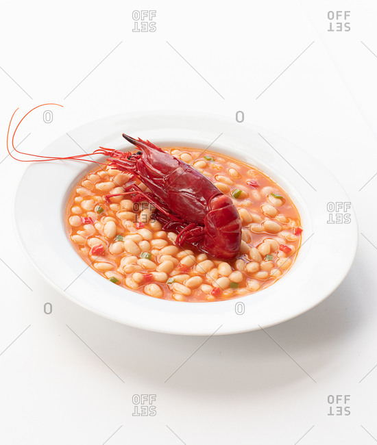 High angle of red boiled crawfish placed in bowl with beans in tomato sauce and served on table in cafe